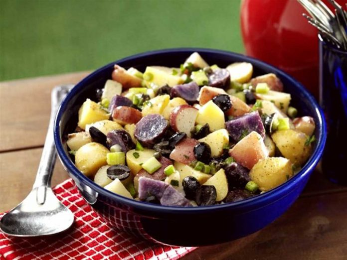 Red White and Blue Potato Salad in a bowl on a picnic table