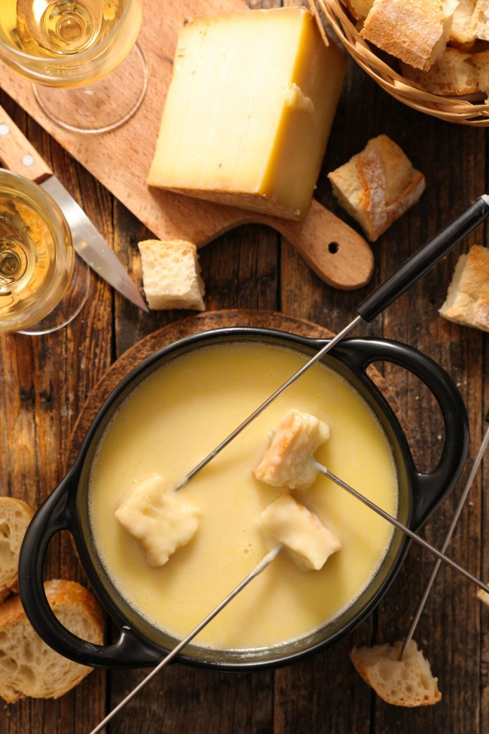 Dipping bread into the Seafood Cheese Fondue pot.