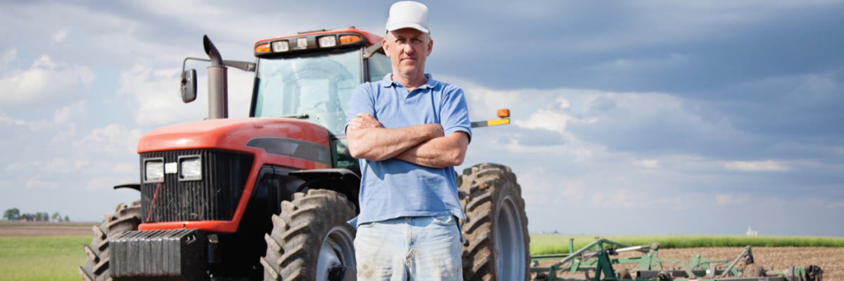Farmer standing by tractor
