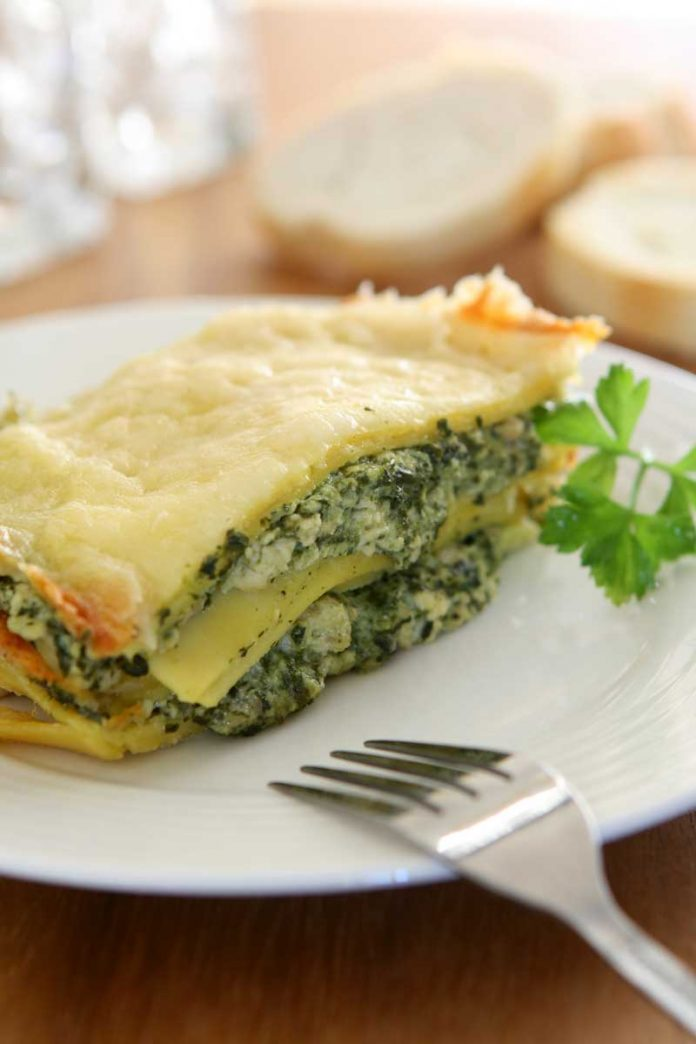A piece of Four Cheese Spinach Lasagna on a white dinner plate.