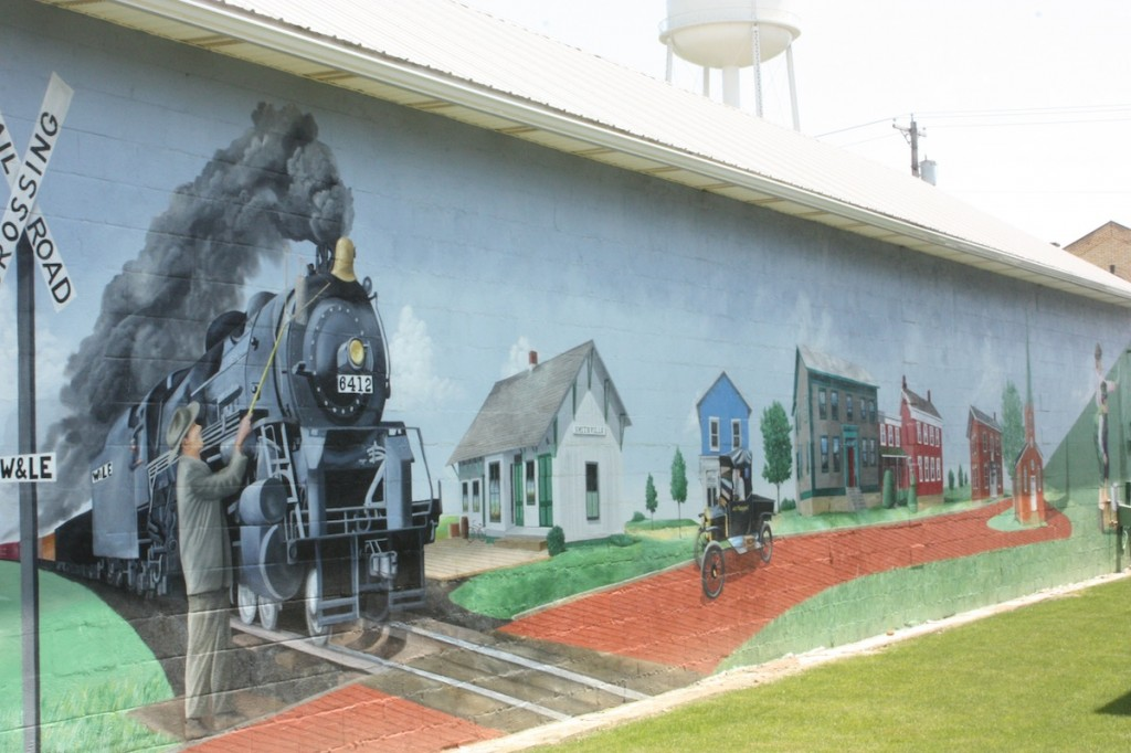 This mural was inspired by an old painting of a man passing a message to the train conductor. The surrounding town in the mural is meant to portray Smithville at the time and is still quite accurate today.