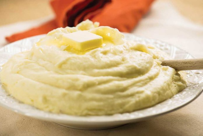 A serving bowl of Cheesy Maple Mashed Potatoes with a pat of butter on top.