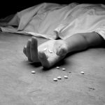 A black and white image of an addict, dead beneath a sheet, arm outstretched, pills in the palm of their lifeless hand and littering the floor near their hand.