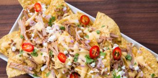 Nachos covered in pulled pork, cilantro, peppers, cheese and other yummy toppings.