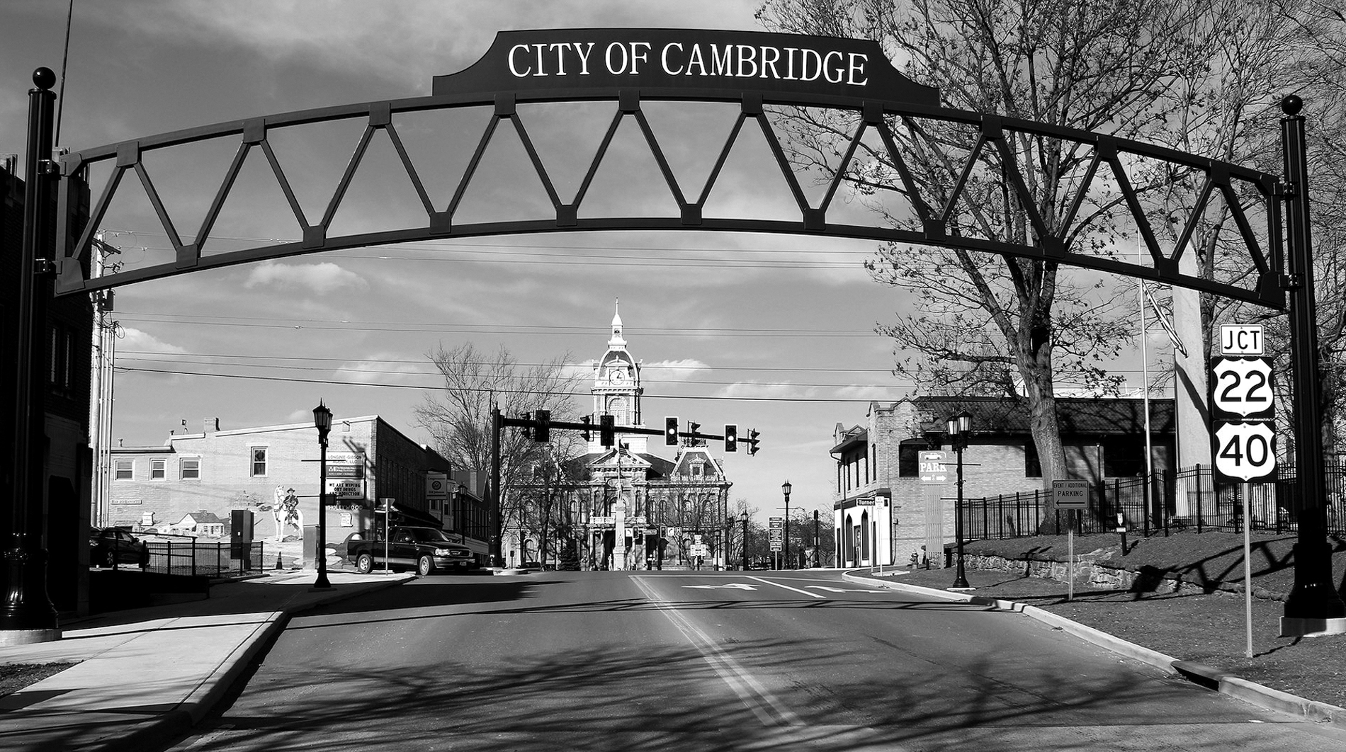 The entrance to the small town of Cambridge, a road leads up over a bride looking into this small town's historic distric. A church is seen in the distance.