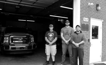 Three volunteer North Beaver Firefighters and Rescue workers stand in front of their station.