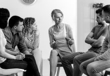 A diverse group of people sit and talk during a group counseling session.