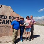 The Bates and Tracy Families pose in front of the entrance for Red Rock Canyon National Park with the Farm and Dairy paper in hand.