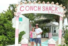 The Willoughbys at the entrance to Da Conch Shack on Turks and Caicos holding a Farm and Dairy Newspaper