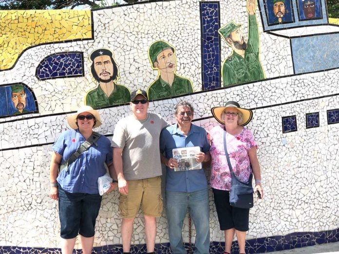 Joyce and John Paglialunga and their children, John and Jeana, stand in front of a mosaic wall depicting Fidel Castro and Guerrillero Heroico.