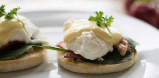 Hollandaise Sauce over poached eggs, spinach, and bacon on an english muffin