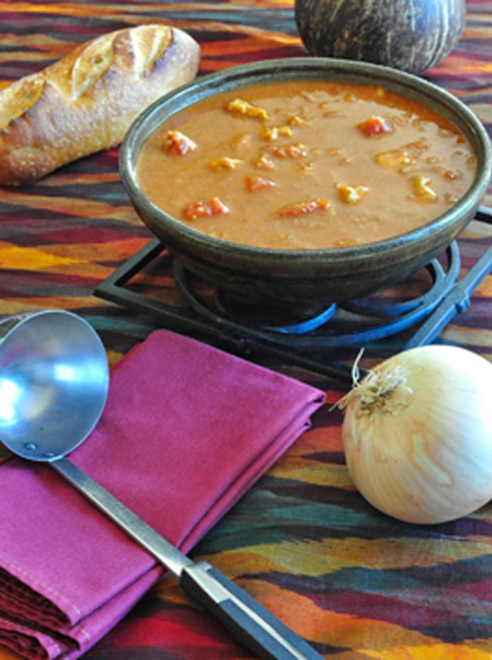 A bowl of West African Peanut Soup with an onion, and ladel in the foreground