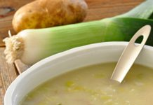 A bowl of Creamy Potato Leek Soup, a leek and poato are in the background and a bulb of garlic is in the foreground