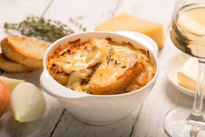 A bowl of French Onion Soup surrounded by onions, crostinis and cheese