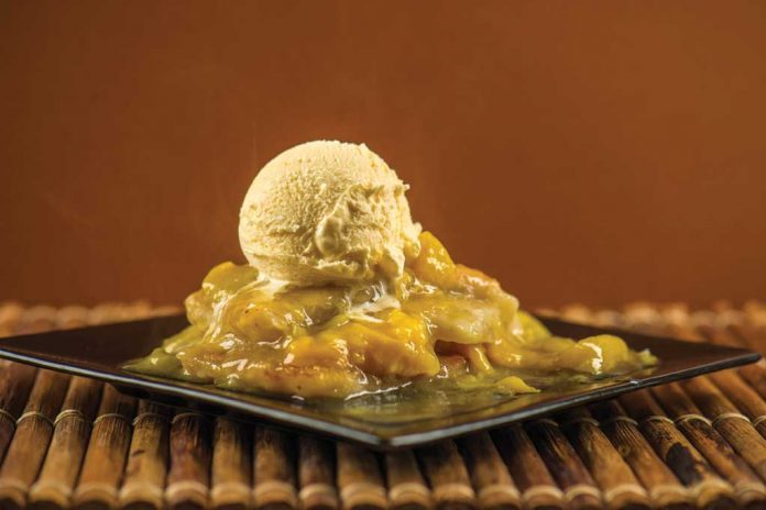 A plate of Slow Cooker Peach Cobbler with a scoop of vanilla ice cream on top