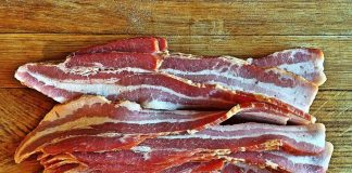 Bacon layed out on a cutting board to be chopped into pieces for Pigskin Bites