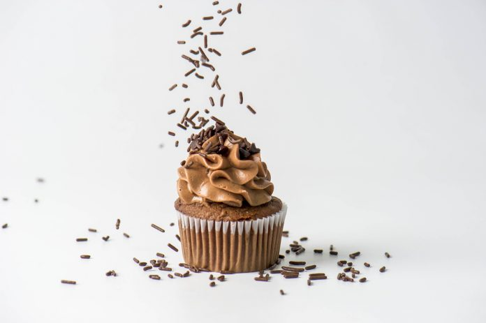 Chocolate Cupcake with Chocolate Cream Cheese Frosting and Chocolate Sprinkles dropping over the top.