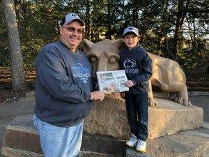 Dennis Hall standing in front of the Nitany Lion Statue at Penn State with his nephew, Jake and his Farm and Dairy.