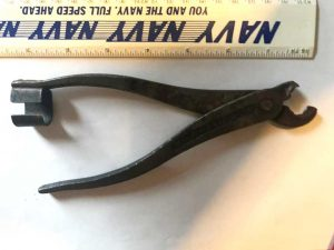Metal plyer like item with a c-shaped piece on the end of one of the arms and curved pinchers that do not sit flat together.