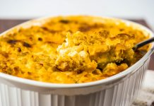 A white casserole dish filled with Macaroni & Cheese