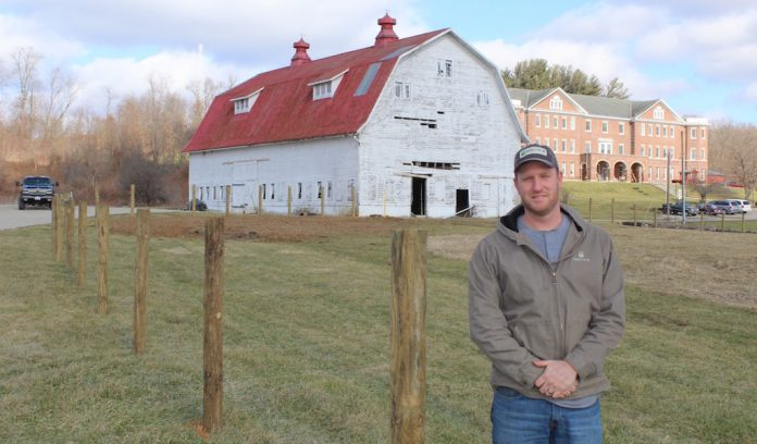 John Lindsey, an FFA adviser at New Lexington, standing in front of school farm.