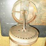 Richard Bader, of Middletown, New York, picked up Item No. 1125 at a yard sale. It is 9 inches in diameter, 6 1/2 inches in height when closed and weighs 12 pounds. There is a lever on the side that you can move to any hole on the disk. The peg on top has a handle and moves back and forth.