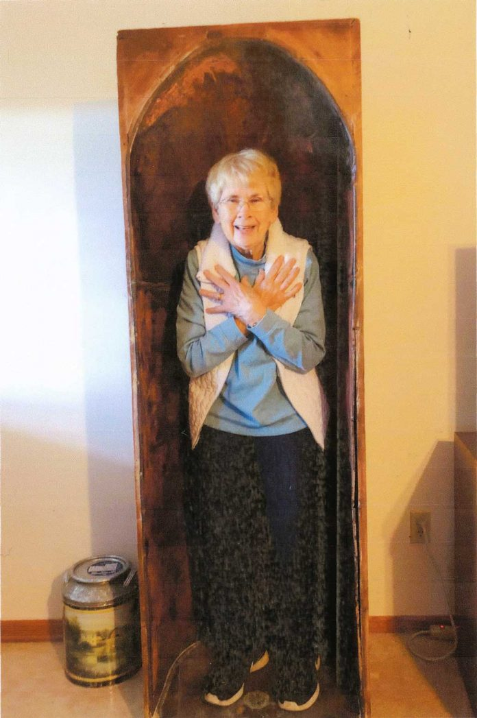 A woman stands inside of a large opening in this antique item.