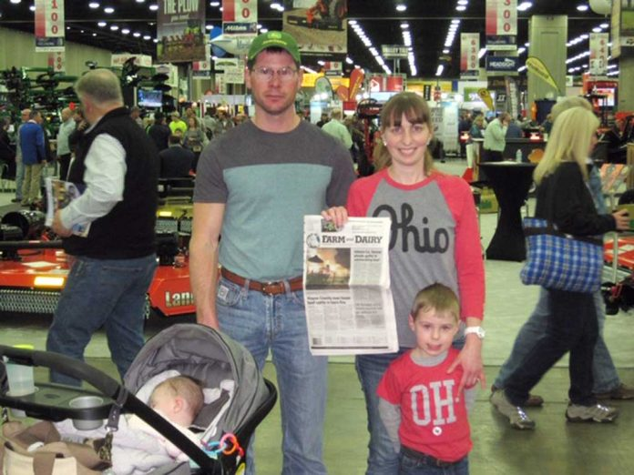 The Hays family stands with their Farm and Dairy Newspaper at the National Farm Machinery Show