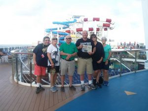 The Swartz family and friends stand on the deck of their cruise ship with the waterslides in the background and a Farm and Dairy in their hands.