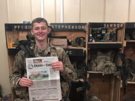 Pfc. Sims poses with his farm and dairy in front of his machine gun while on deployment in Afghanistan
