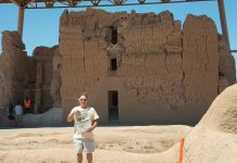 Bill Henry stands in front of the Casa Grande Ruins holding a Farm and Dairy newspaper.