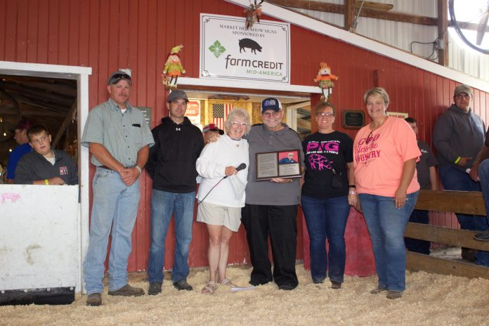 Darell Furlong stands with Ginny Barker and members of the hog committee after they recognized him with a plaque for his retirement.