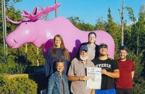 The Rhoades family pose in front of the Pink Moose statue on Mackinaw Island