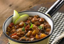 A bowl of Apple Turkey Chili garnished with two apple slices.