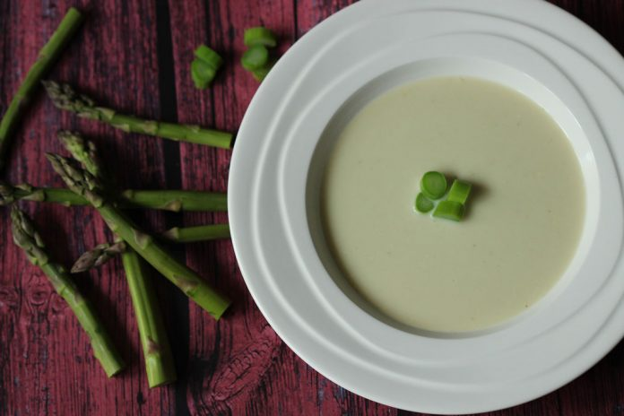 A bowl of light green soup with slices of asparagus in the center and shots on the table beside the bowl