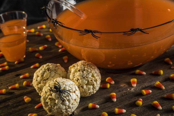 Caramel Popcorn Balls decorated for halloween with plastic spiders