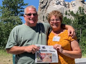 Tom White and Elizabeth Burrier stand in front of Mt. Rushmore with their Farm and Dairy newspaper in hand.