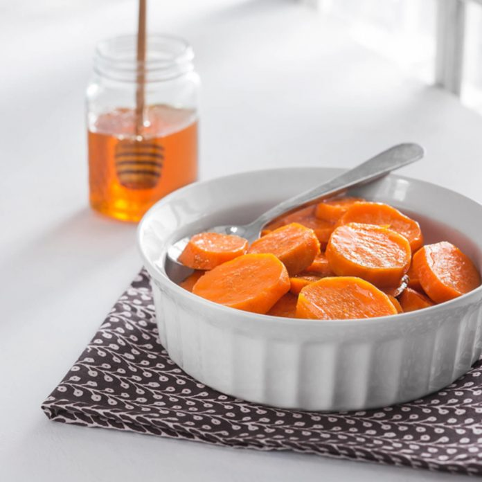 Candied Yams in a white serving dish with a glass honey container and dipper behind it.