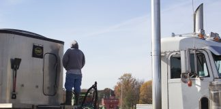 A farmer stands on a semi truck, watching combines harvest.