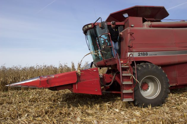 A farmer climbs out of a combine.