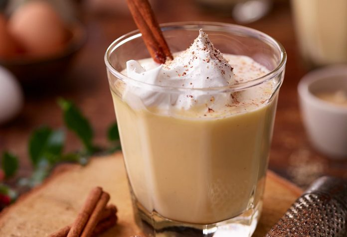 A glass of egg nog with whipped topping and a cinnamon stick garnish