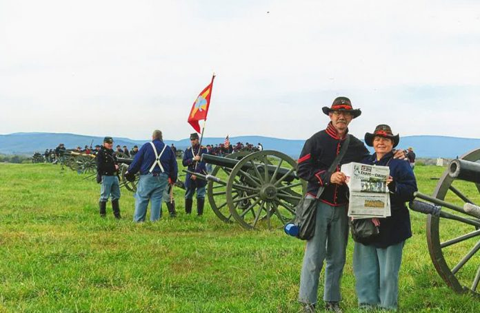 The Dazeys stand dressed in Union soldier uniforms on the battle field. A group of Union soldiers stand behind them near an Civil War era cannon.