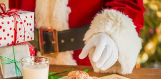 Santa reaching for cookies on a plate with a glass of milk nearby