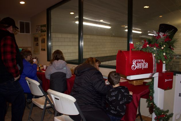 Children work on letters for Santa next to the mailbox.