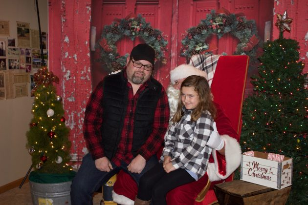 Avalynn Bloomfield and Richard Bloomfield, her dad, sit on Santa's lap together.