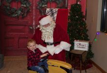 A child sits on a yellow toy tractor in front of Santa.