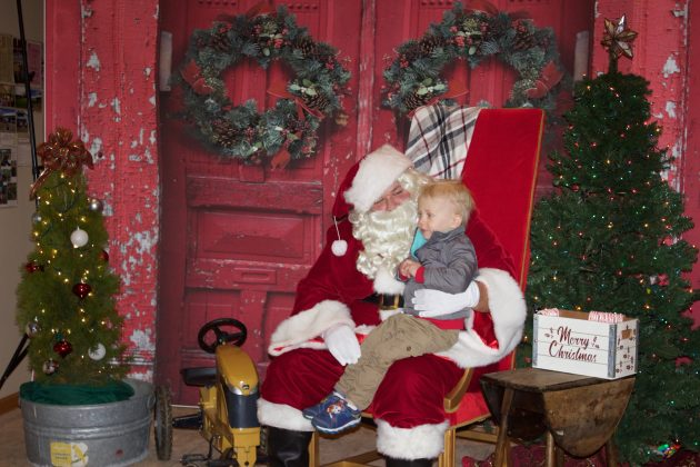 A two-year-old blonde boy sits on Santa's lap.
