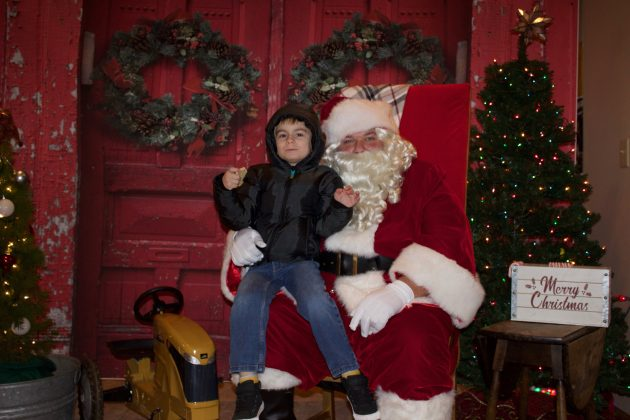 A boy with a black jacket and hood sits on Santa's lap for a picture.