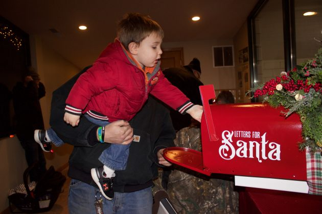 A boy puts a letter for Santa into a mailbox while his father holds him up so he can reach.