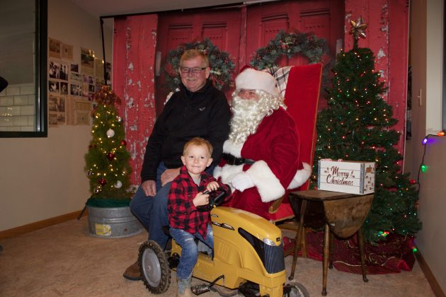 A grandfather sits on Santa's lap while his grandson sits on a yellow toy tractor in front of them.